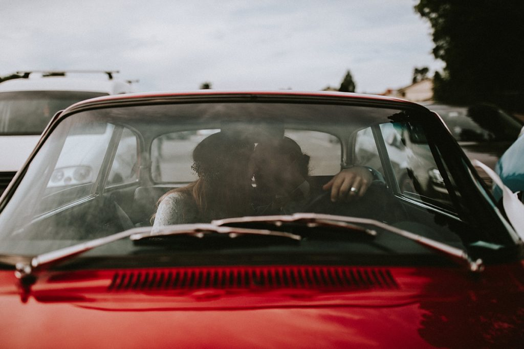 bridal couple in vintage wedding car